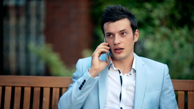 Young businessman talking on the phone in the park video