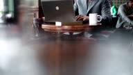 Young businessman typing at laptop and drinking coffee. video