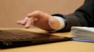 Young businessman using a laptop and writing a note video