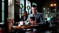 Young businessman using digital tablet at the cafe. video