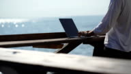 young businessman using his laptop on the waterfront on sea background video