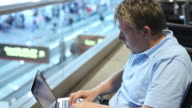 Young businessman using laptop at airport video