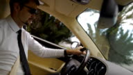 Young businessman wearing sunglasses driving cool car, beautiful view on city video