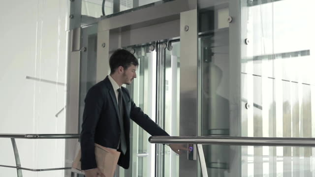 Young businessman with documents wait the elevator video