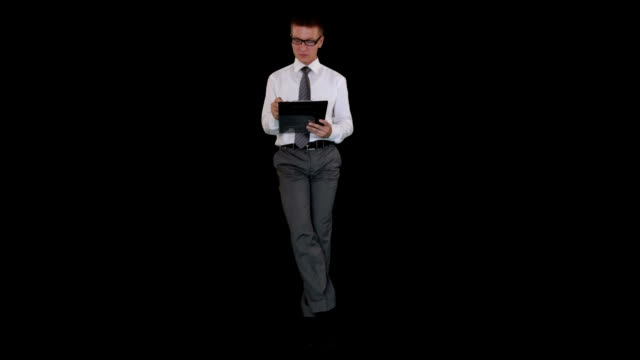 Young businessman with glasses writting on a clipboard and sitting, against black video