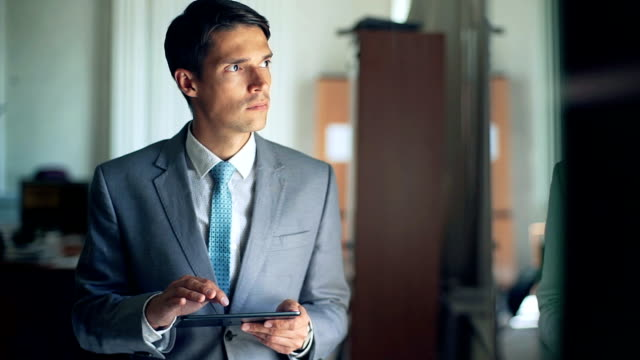 Young businessman with tablet in the office video
