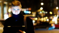Young businessman with the tablet against the night traffic video