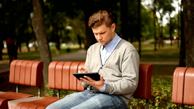 Young businessman working on tablet computer in city park video
