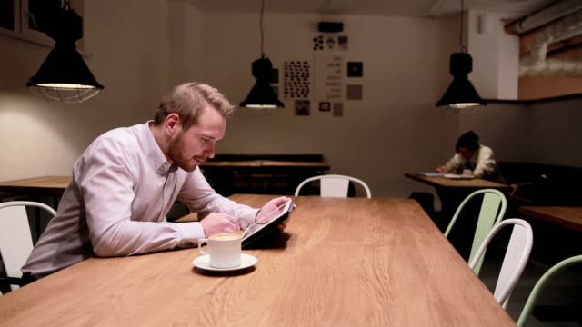 Young businessman working on tablet  in cafe video
