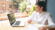 Young businesswoman architect working in a coffee shop. video