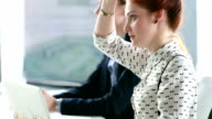Young businesswoman at office meeting, applauding after colleagues presentation video