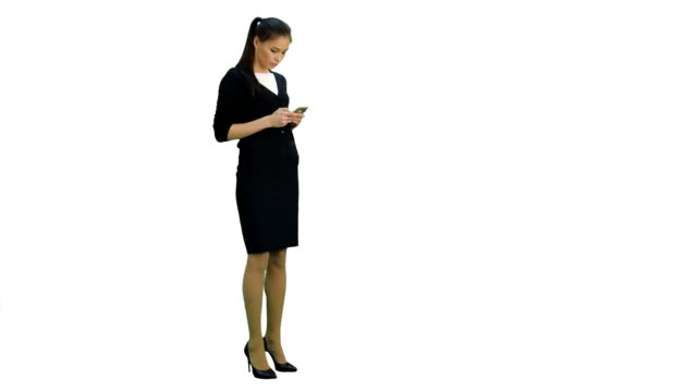 Young businesswoman checking her mobile phone while walking on white background video
