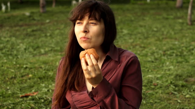 Young businesswoman eating a little burger sitting on the grass in the park video