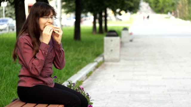 Young businesswoman eating a small burger sitting on a bench in the park video