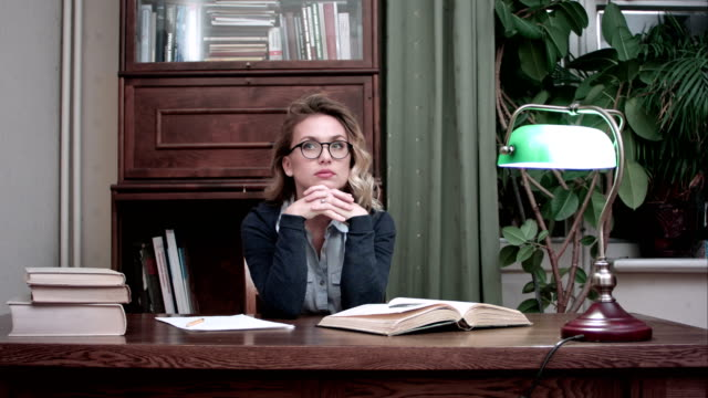 Young businesswoman in glasses thinking over her project and suddenly having a genius idea video