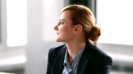 Young businesswoman listening and nodding during corporate presentation video