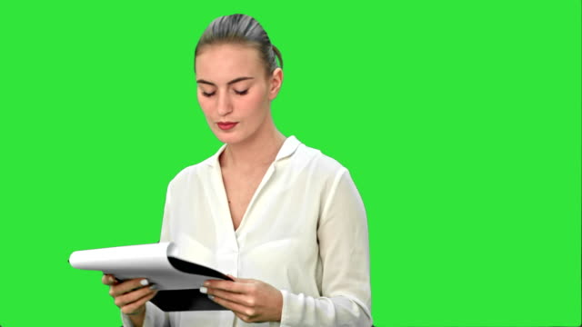 Young businesswoman reading documents on a Green Screen, Chroma Key video