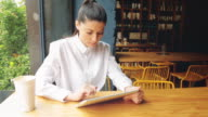 Young businesswoman using digital tablet in a coffee shop. video