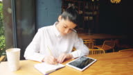 Young businesswoman working in a coffee shop, writing notes and using digital tablet. video