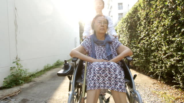 Young caregiver take care elderly woman on wheelchair video