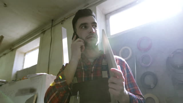 4K A young carpenter in the joinery uniform is talking on a mobile phone in the woodworking industry room. video