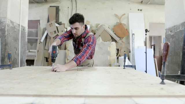 4K A young carpenter turning the self-tapping screw with a screwdriver at a furniture production. video