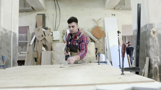 4K A young carpenter works at a woodworking factory. video