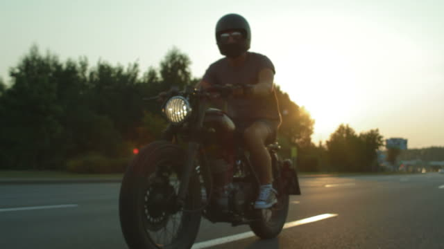 Young caucasian biker riding a custom built cafe racer motorcycle, side view stabilized footage video