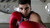 Young caucasian boxer in red gloves is expecting a fight. video