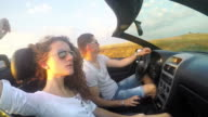 Young Caucasian couple fun driving luxury cabriolet convertable car. SLOW MOTION stock footage video