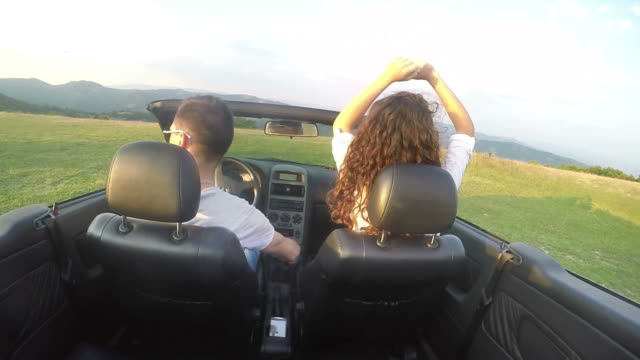 Young Caucasian couple fun driving luxury cabriolet convertible car. SLOW MOTION stock footage video