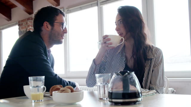 young caucasian couple in love talking while having italian breakfast and american coffee indoor in modern industrial house.4k handheld video shot video