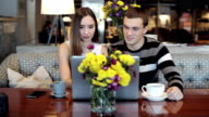 Young caucasian couple with modern laptop in cafe video