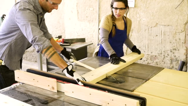 Young Caucasian male and young Hispanic woman cut board with table saw video