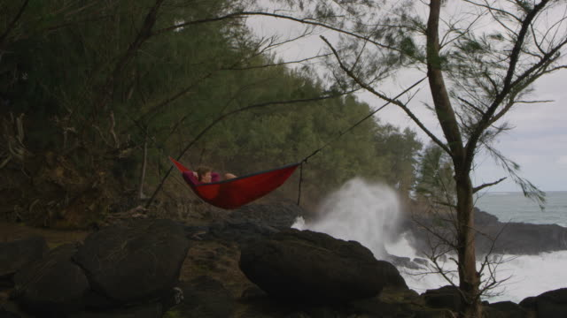 Young caucasian man relaxing in hammock next to ocean video