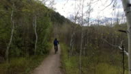 A young Caucasian man rides his bicycle on a mountain trail video