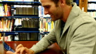 Young Caucasian man with a digital tablet studies in college or local public library video