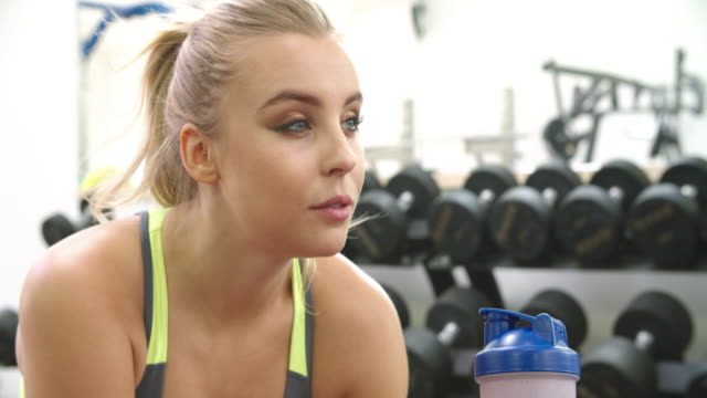 Young caucasian woman drinking a protein shake at a gym video