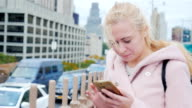 A young Caucasian woman in a large New York City. Is typing on a smartphone on the background of skyscrapers and road traffic video