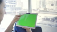 Young caucasian woman in her 30s using her tablet to be online with green screen video