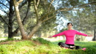 young caucasian woman practicing meditation in the park video