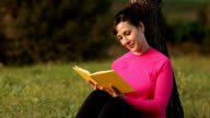 young caucasian woman reading book in the green park video
