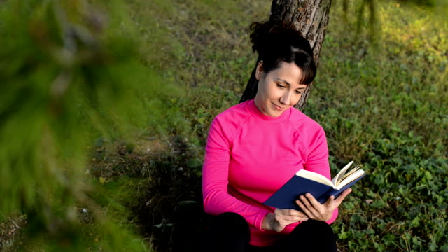 young caucasian woman reading book in the park video