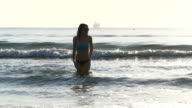 Young caucasian woman running in the water towards beach in slow motion video