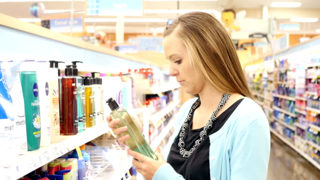 Young Caucasian woman shops for body wash in personal care aisle of supermarket video