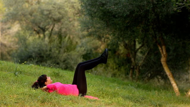 young caucasian women doing abdominal exercise outdoors in the nature video