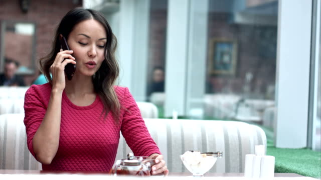 Young charming woman calling with cell telephone while sitting alone in cafe video