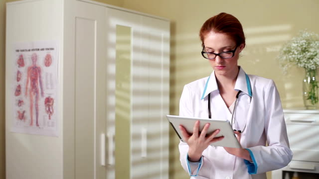 Young charming woman doctor using tablet in the medical interior. Dolly shot. video