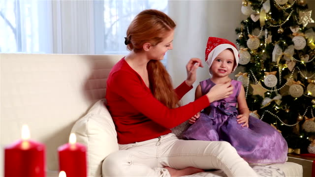 Young charming woman wears a red Christmas hat his daughter. video