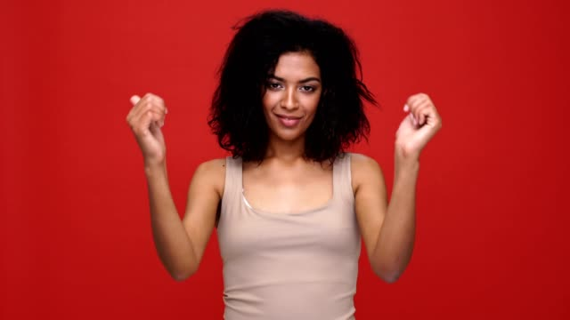 Young cheerful african woman showing thumbs up over red background. video
